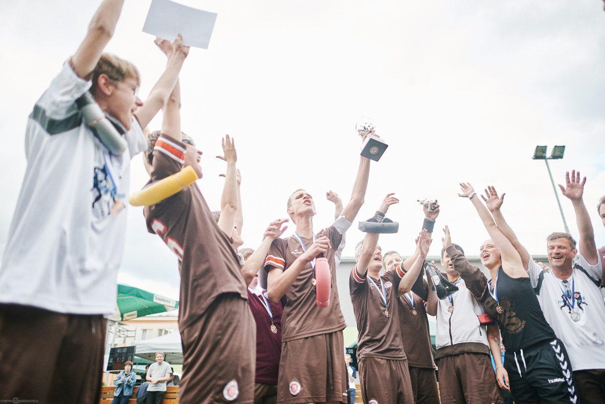 Das Team jubelt und hält den Pokal in die Höhe