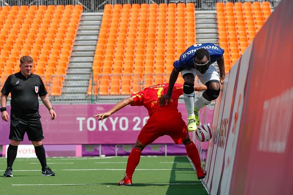 Spielszene aus der Begegnung China-Frankreich. Der französische Spieler Wouandji hebt rechts im Bild an der Bande mit Ball über dem chinesischen Gegenspieler Yu ab. Schiedsrichter Stuart Winton bestaunt die Szene links im Bild.