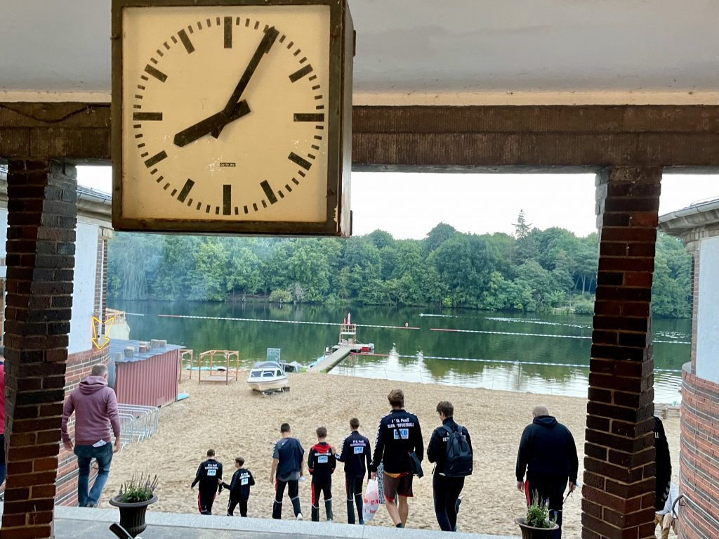 Das Team auf dem Weg zum Plötzensee. Im Vordergrund zeigt eine Uhr kurz nach 8. Im Hintergrund See mit Sandstrand