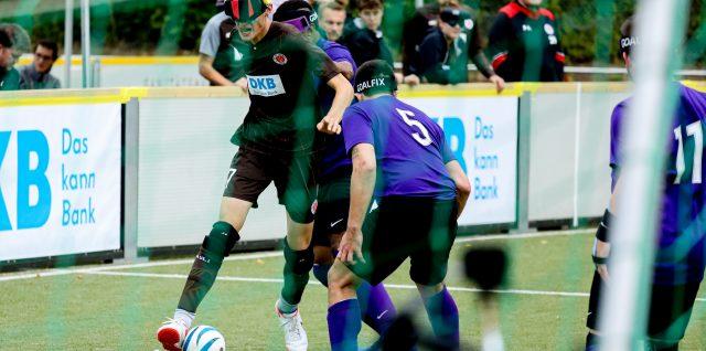 Rasmus dribbelt auf einen englischen Spieler zu. Im Hintergrund verfolgt das FCSP-Team gespannt das Geschehen